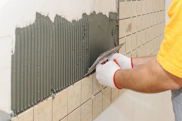 Worker instiling tiles on the wall in the kitchen.