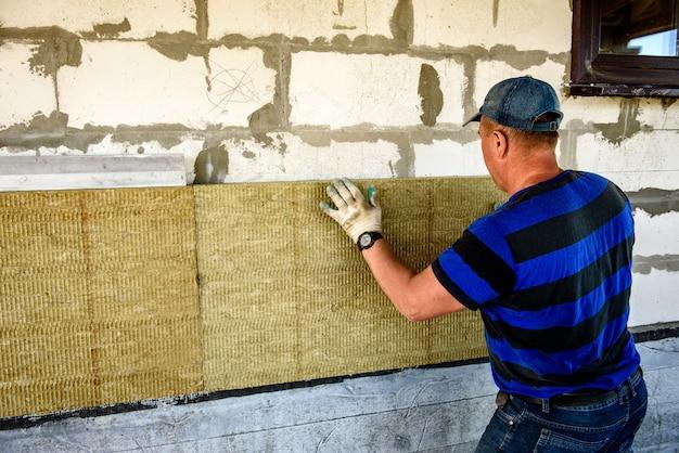 Рабочий утепляет дом плитами из минеральной ваты. внутренняя теплоизоляция стен минеральной ватой.