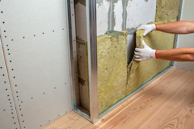 Рабочий утепляет стену комнаты теплоизоляцией из минеральной ваты.