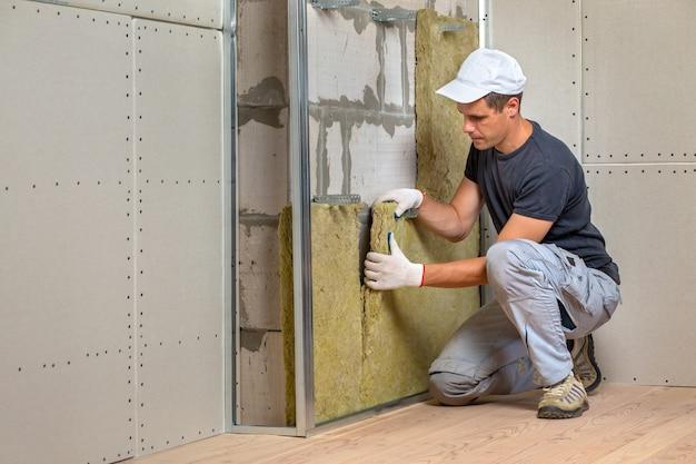 Рабочий изолирует стену помещения теплоизоляцией из минеральной ваты.