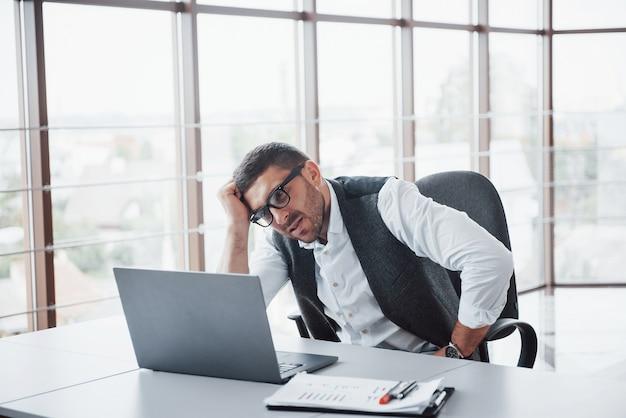 작업자는 사무실에서 노트북을 가진 젊은 남자입니다.