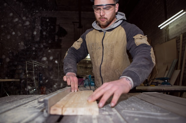 A worker is concentrating on processing a wooden board on a circular machine