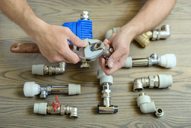 A worker is connecting elements of the plumbing.