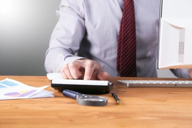 Рабочий рассчитывает на калькулятор, сидящий за своим столом.