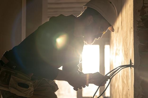 Рабочий режет провода плоскогубцами