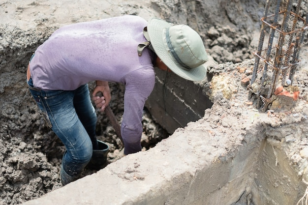A worker is digging a hole by usinf hoe / house construction