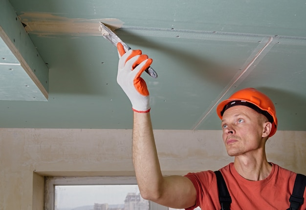 The worker is filling the plasterboards seams with gypsum putty