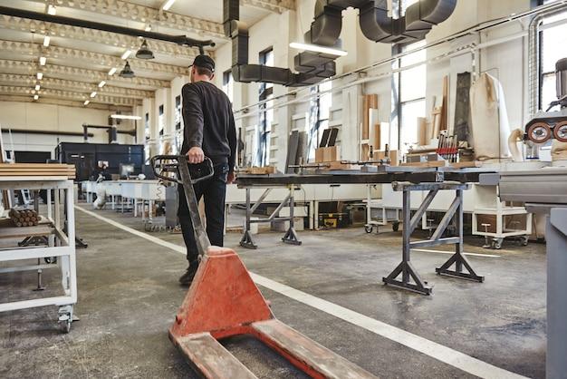 Рабочий собирается загружать поддоны с помощью домкрата для поддонов концепция транспортировки вид сзади