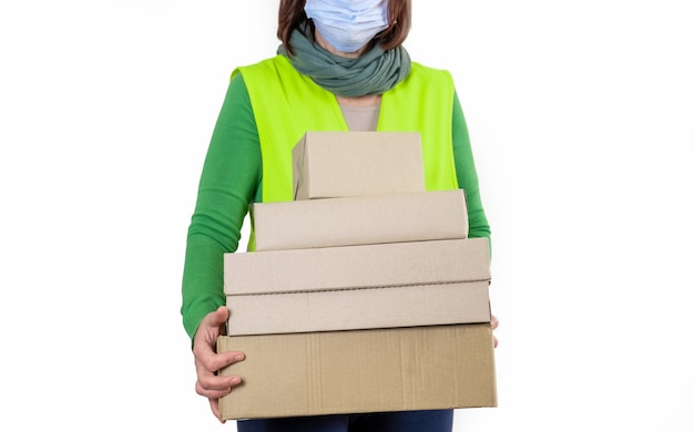 Worker is in a green vest holding a lot of paper boxes, delivery concept.
