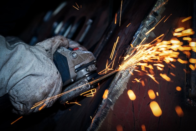 The worker is grinding metal with an angle grinder