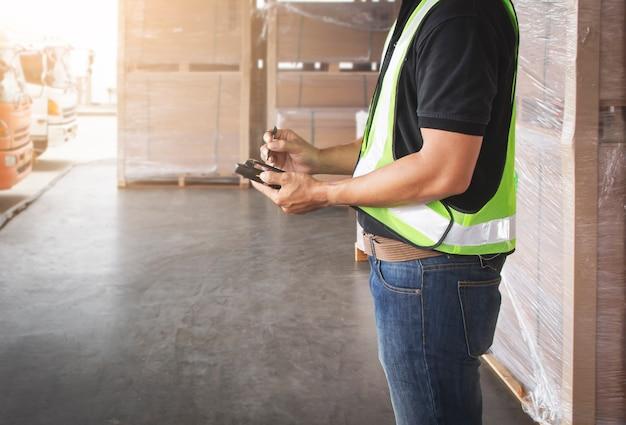 Рабочий держит смартфон и общается с клиентом, занимающимся отгрузкой на складе.