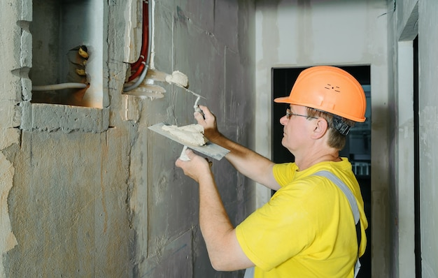 The worker is holding trowels with a gypsum