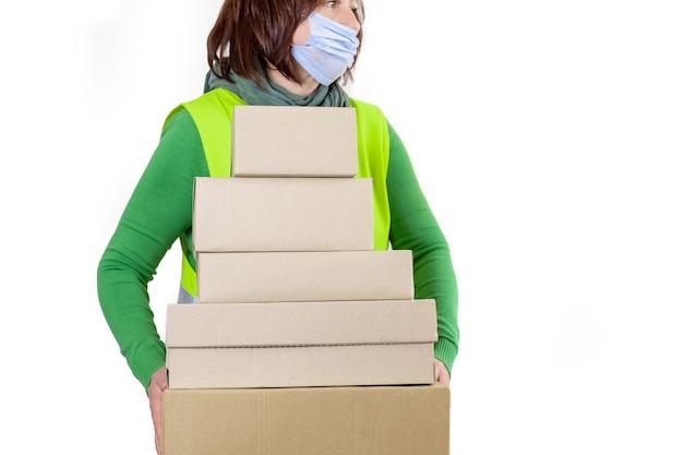 Рабочий в зеленом жилете, держащем много бумажных коробок, концепция доставки.