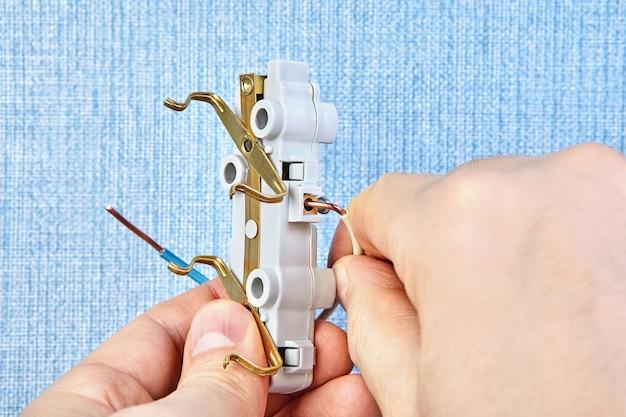 Рабочий устанавливает электрическую разводку в доме.
