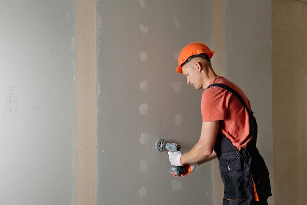The worker is making holes in the drywall