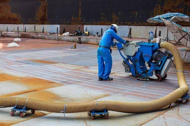 作業員は、機器エンジンの空気圧サンドブラストによってペイントルーフタンクを取り外しています