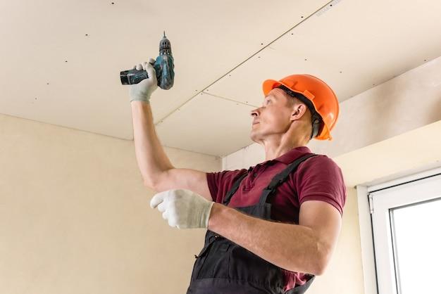 Рабочий с помощью шурупов и отвертки прикрепляет гипсокартон к потолку.