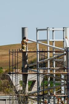 足場で労働者が金属構造を溶接している間、労働者は建設現場で働いています