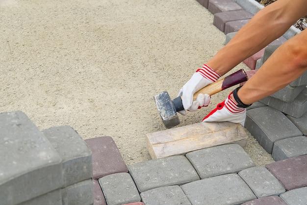 敷石を敷設する労働者。石畳、砂の上に石畳の岩を置く建設労働者。