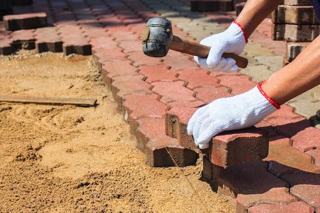 Рабочий кладет красные бетонные брусчатки.