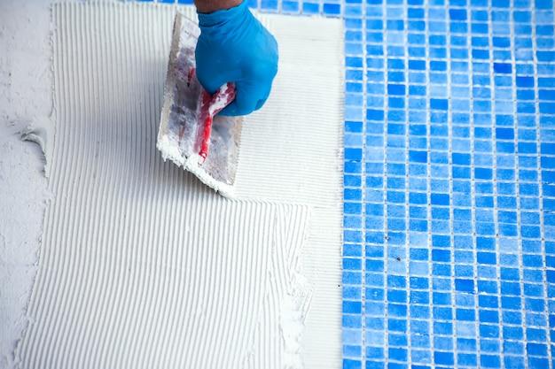 수영장에 타일을 깔고 있는 작업자. 수영장 수리 작업.