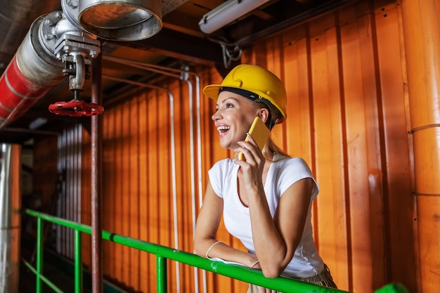 Рабочий, опираясь на перила в теплоцентрали и разговаривая по телефону