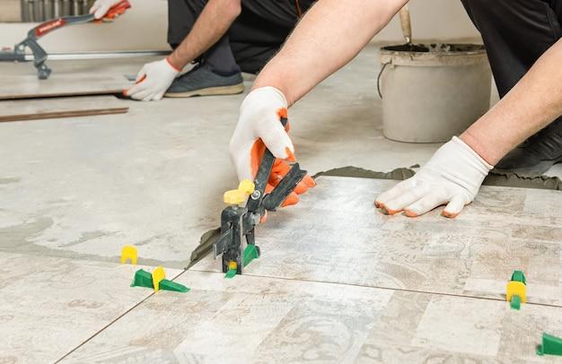 Рабочий выравнивает керамическую плитку клиньями и зажимами