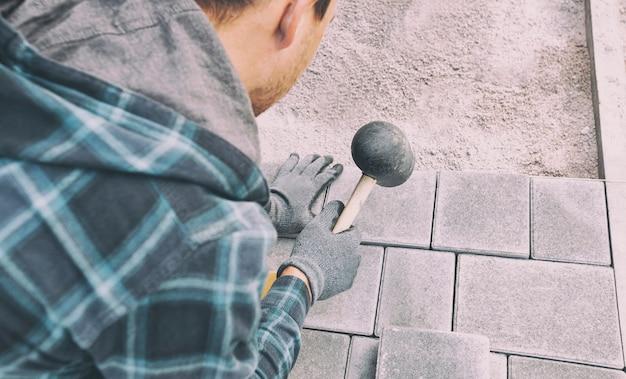 Работник облицовки дорожки тротуарной плиткой