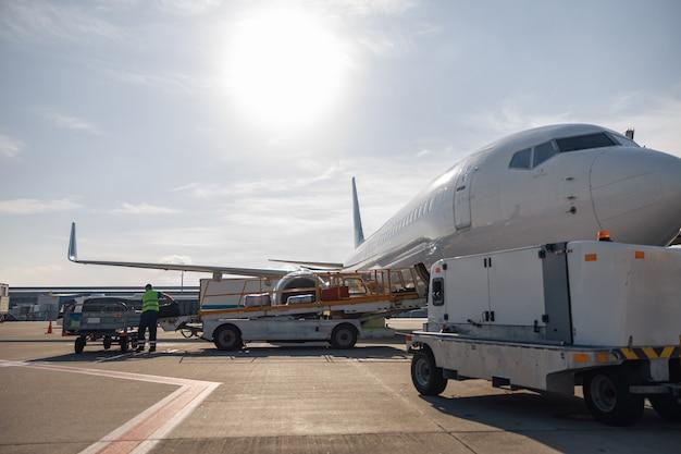 낮에 야외에서 비행기로 컨베이어 벨트에 수하물을 싣는 작업자. 비행기, 운송, 운송 개념