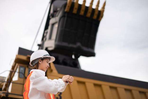 Рабочий смотрит на часы на запястье при добыче бурого угля или угля с грузовиком, перевозящим уголь.