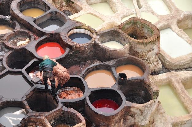 労働者は皮をタンクに降ろしますフェズモロッコで最も古い皮なめし工場で着色された革のペンキが付いている陶磁器の容器