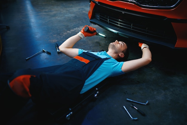 Рабочий, лежащий под автомобилем, автосервис