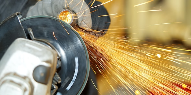 Worker makes metal steel pipe grinding, close-up many sparks