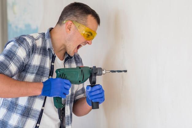 Работник делает отверстие в стене