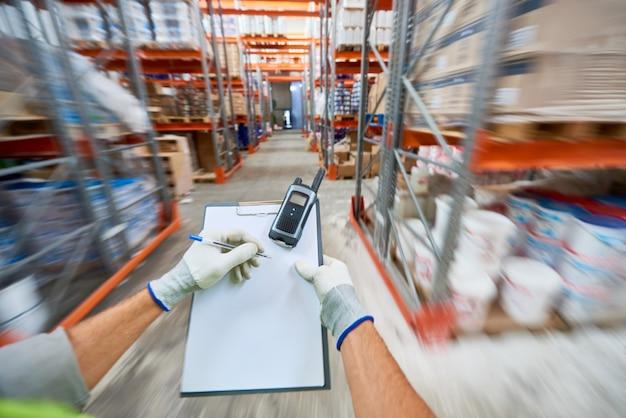 倉庫でメモを作っている労働者