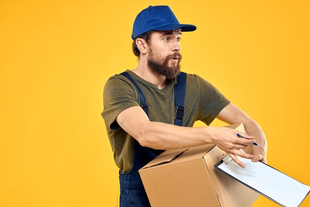 Worker male courier delivering boxes packaging documents yellow space.