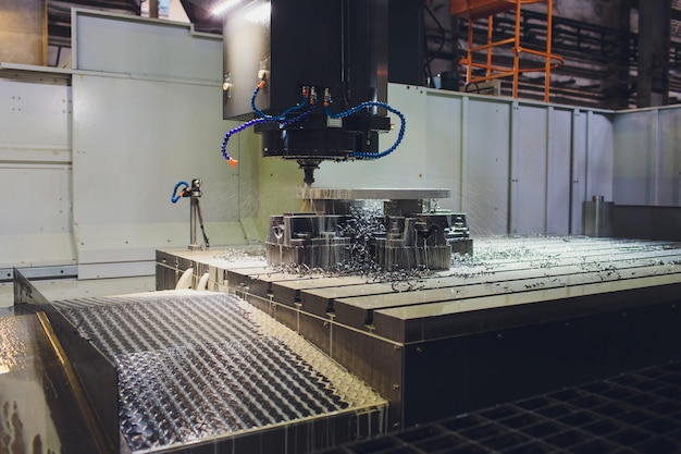 Worker male hands working with cnc machine at factory with lathes.