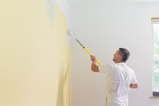 Рабочий наносит краску и шпаклевку на стены в квартире, делает ремонт в новом доме