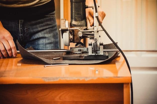 Рабочий мужчина разрезает металлическую трубу на две части, и много искр летят прямо в камеру крупным планом.