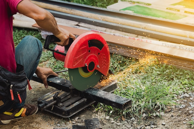 Worker man cutting steel with a circular steel cutter.