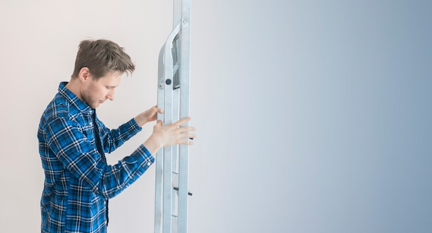 A worker man holding the aluminium ladder against the wall in the new house Premium Photo