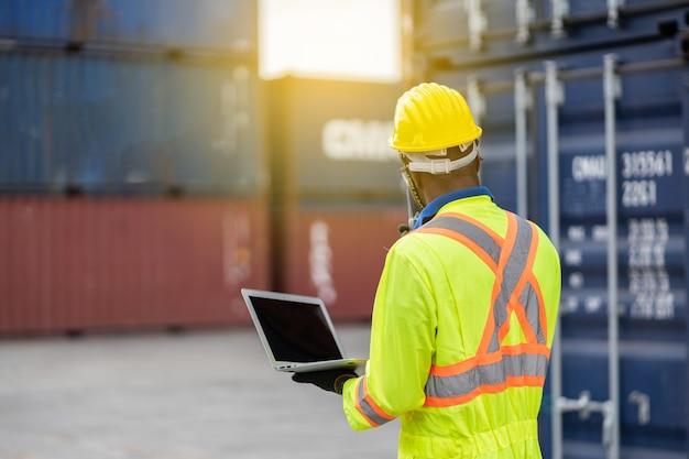 黄色いヘルメットと保護安全ジャンプスーツの制服を着た労働者の男と貨物輸送倉庫でラップトップチェックコンテナを使用します。輸送輸入、輸出物流産業サービス