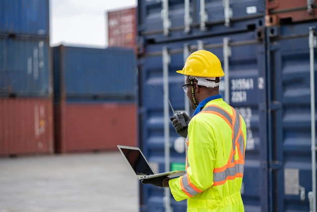 黄色いヘルメットをかぶった保護安全ジャンプスーツの制服を着た労働者の男性は、貨物輸送倉庫でトランシーバーチェックコンテナを使用します。輸送輸入、輸出物流産業サービス