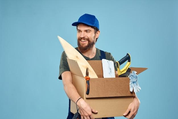 Рабочий человек в униформе коробки инструменты строительство синюю стену.