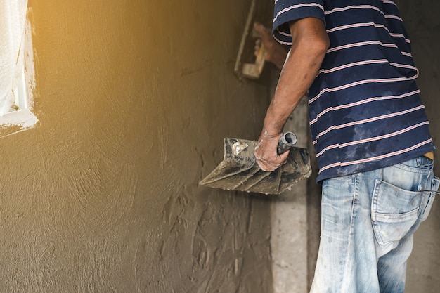 こてで壁を漆喰で塗る労働者の手の