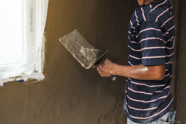 Worker man's hand plastering a wall with trowel