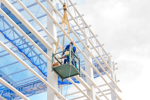 Worker man on a scissor hydraulic lift table platform towards a factory roof