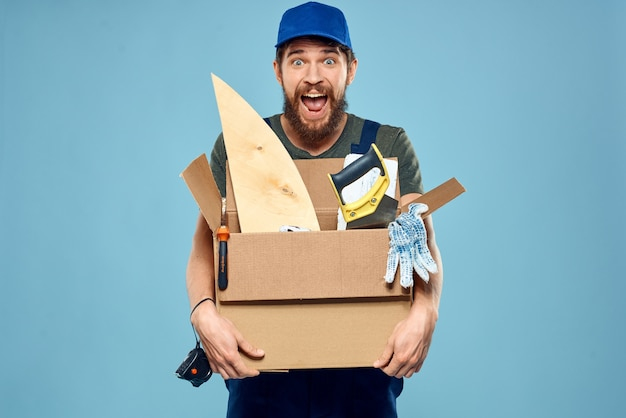 Worker man in uniform box tools construction blue space.
