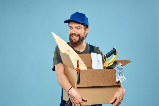 Worker man in uniform box tools construction blue wall.