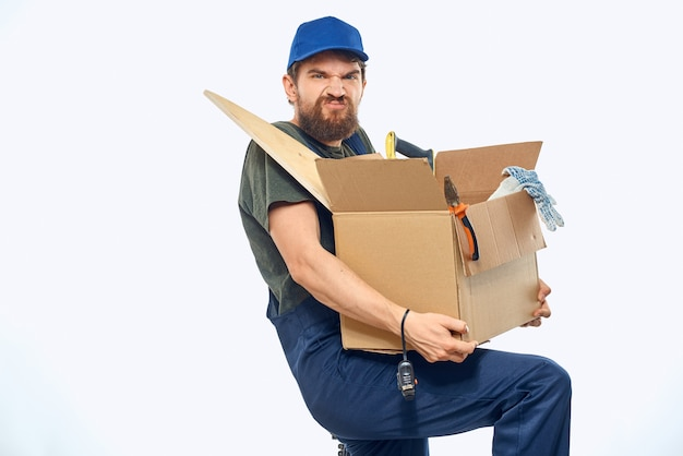 Worker man in uniform with a box in his hands tools delivery service